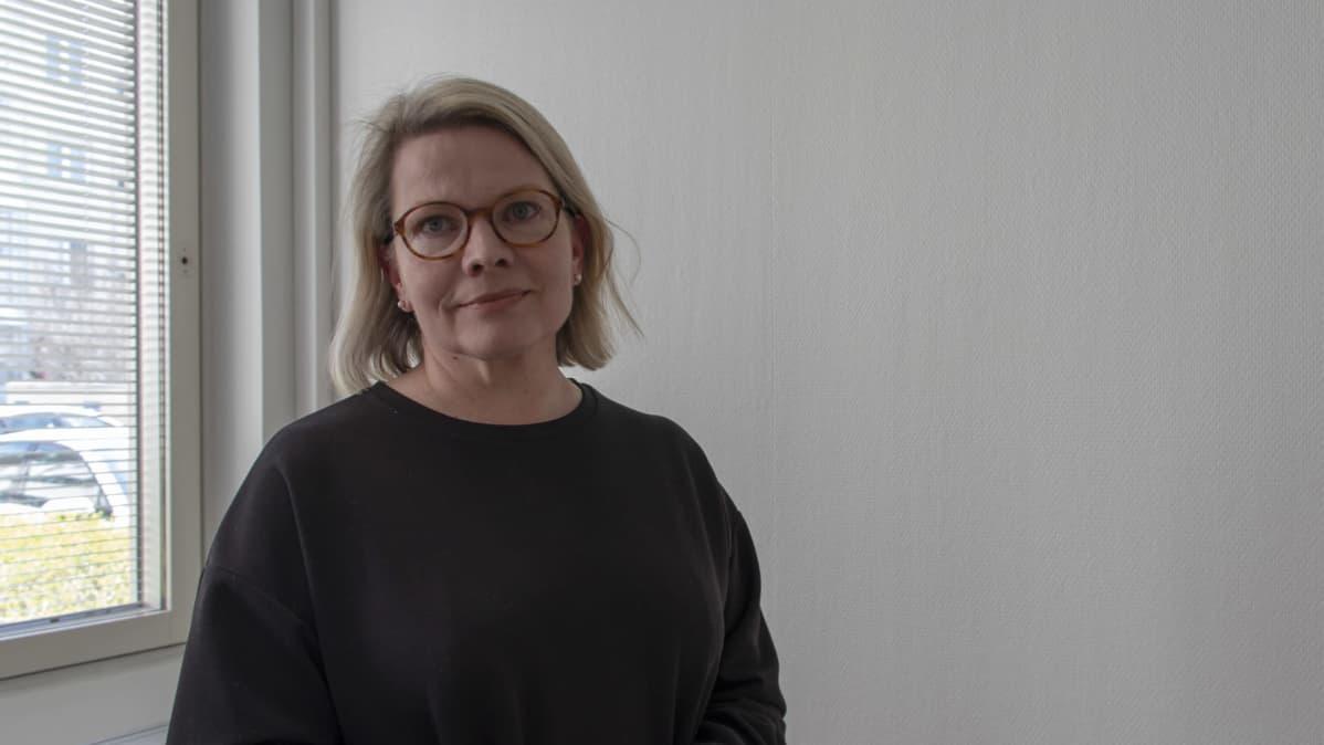 Anne Penttilä katsoo kameraan työhuoneessaan