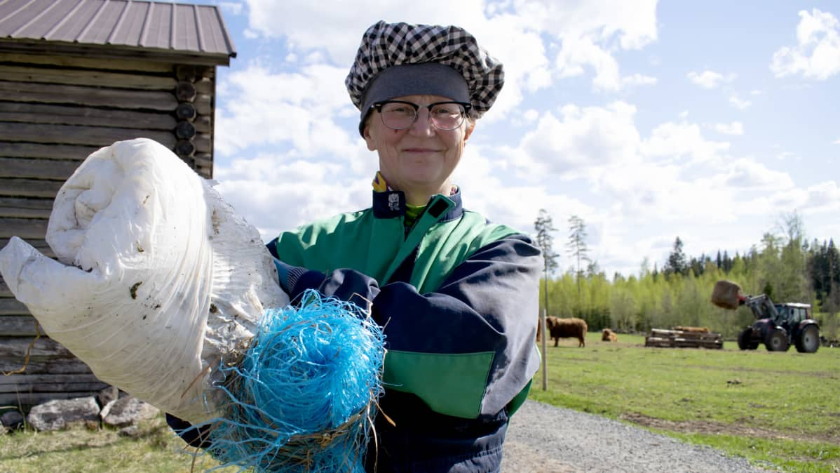 Pyyvin tilan emäntä Marjo Marttinen kantaa käytettyjä paalimuoveja