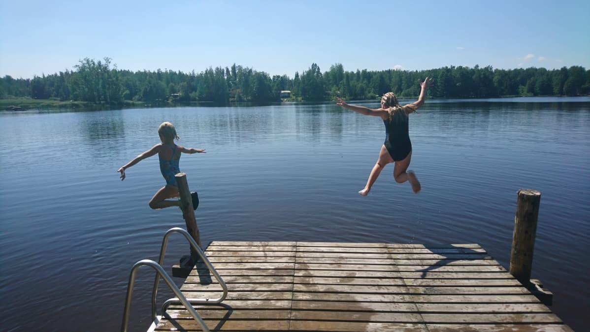 Tyttöjä uimassa järvellä helteellä. Tytöt hyppäävät järveen.
