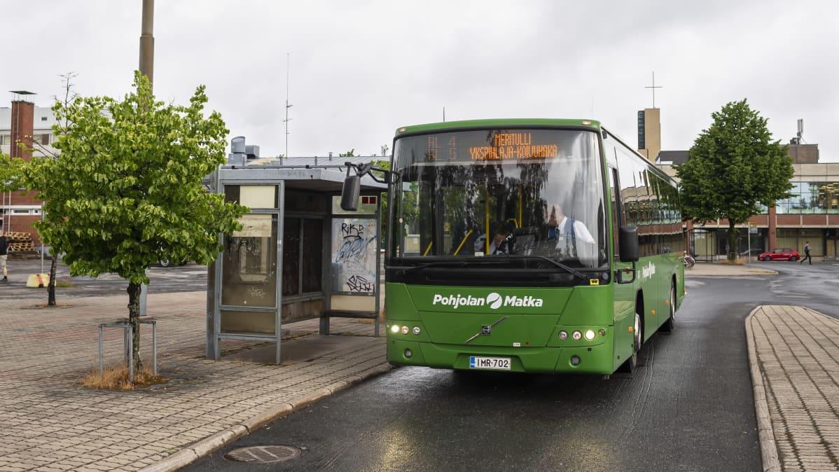 Vihreä linja-auto bussipysäkillä.