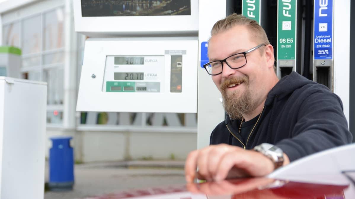 Antti Heikkinen tankkaa autoa ja hymyilee.