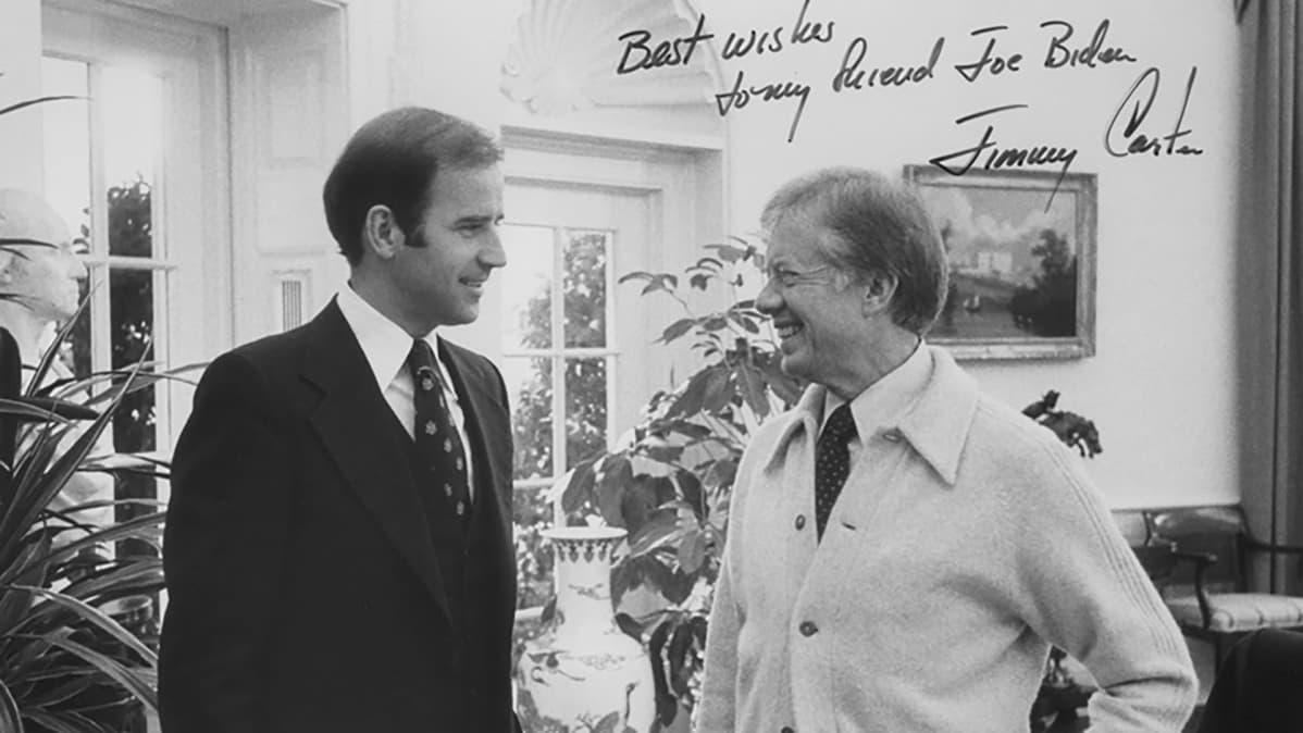 """Mustavalkoinen kuva senaattori Joe Bidenistä ja USA:n presidentti Jimmy Carterista 1970-luvulla. He seisovat vastakkain rennon oloisesti ja hymyilevät. Kuvaan on kirjoitettu käsin: """"Parhaat terveiset ystävälleni Joe Bidenille. Jimmy Carter."""""""