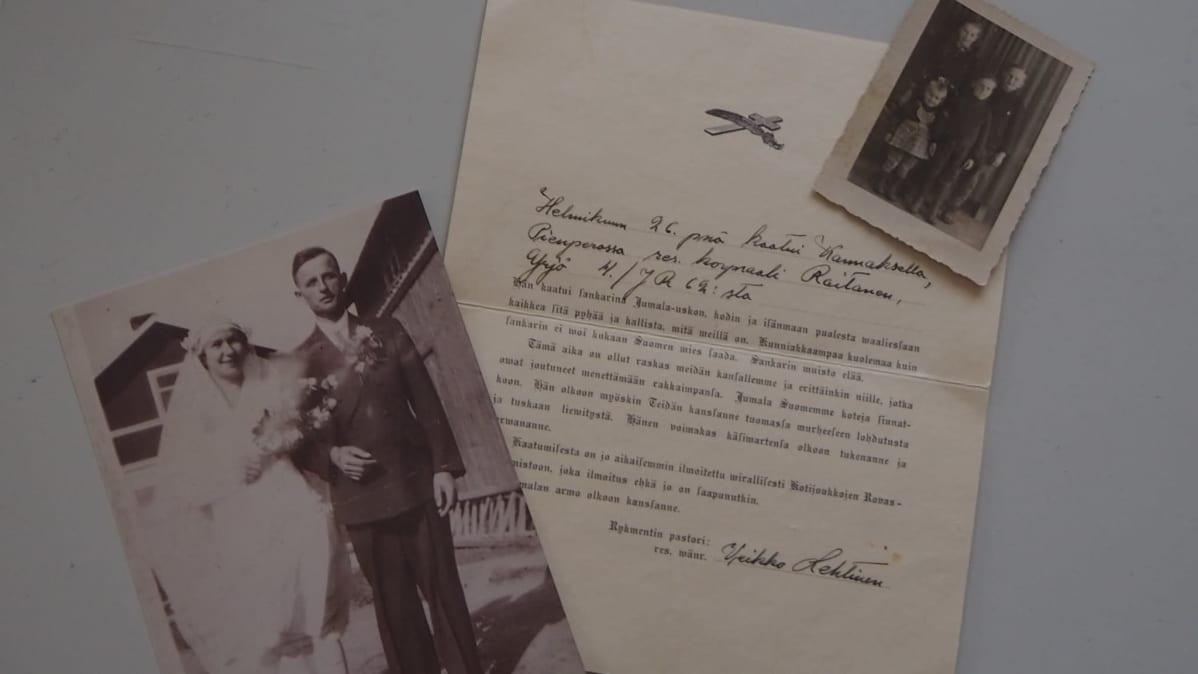 Pöydällä sodassa kaatuneen Yrjö Raitasen hääkuva, kirje rykmentin pastorilta ja valokuva perheen lapsista.