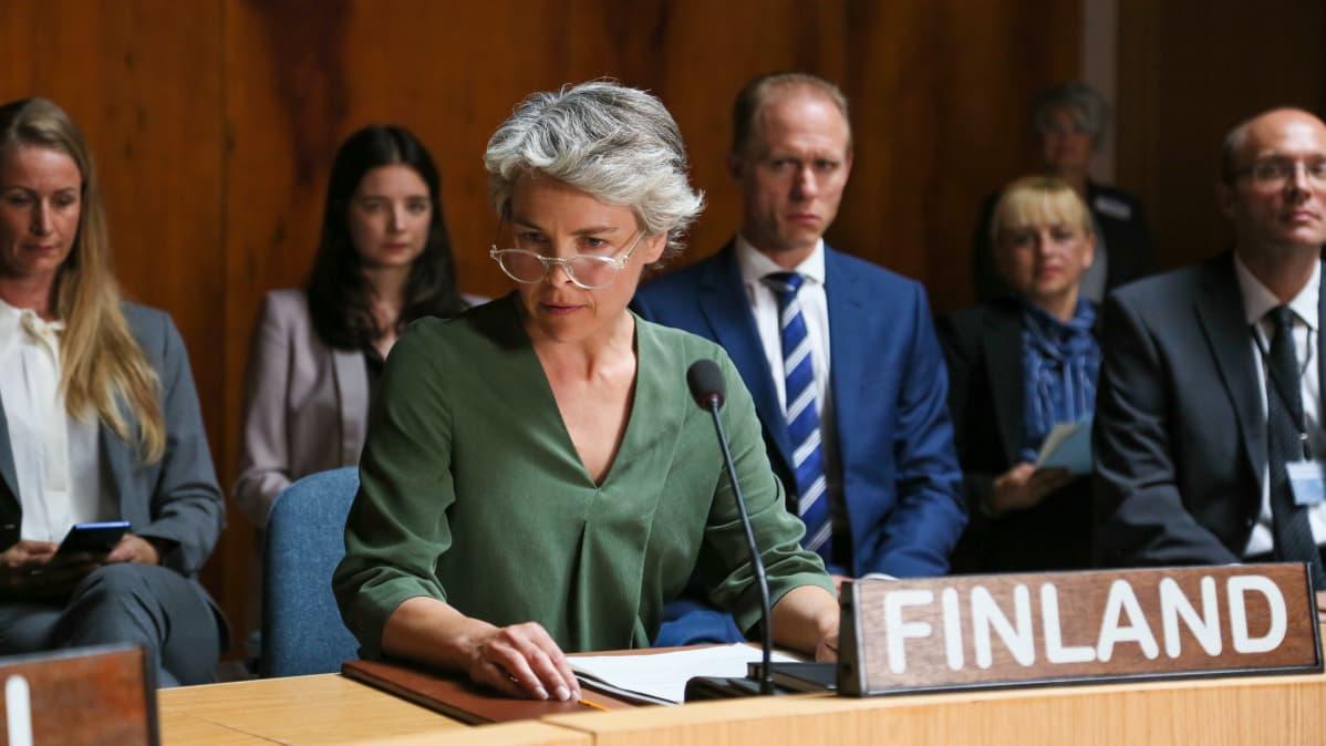 Ann-Mari Sundell (Irina Björklund) istuu vakavana rauhanneuvottelusalissa takanaan ihmisiä.