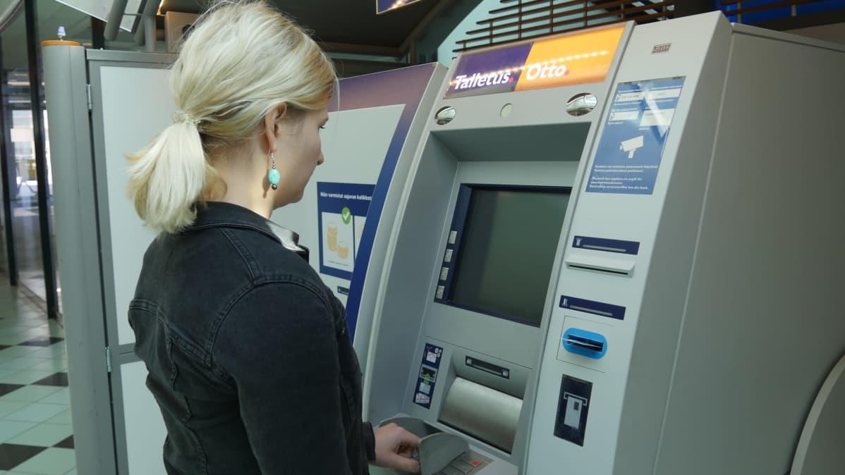 Nainen pankkiautomaatilla nostamassa rahaa.