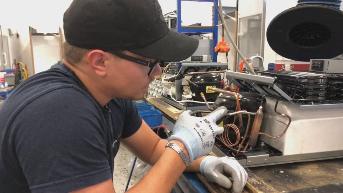 Aste Coolersin työntekijä tekee töitä kylmäkompressorin parissa.