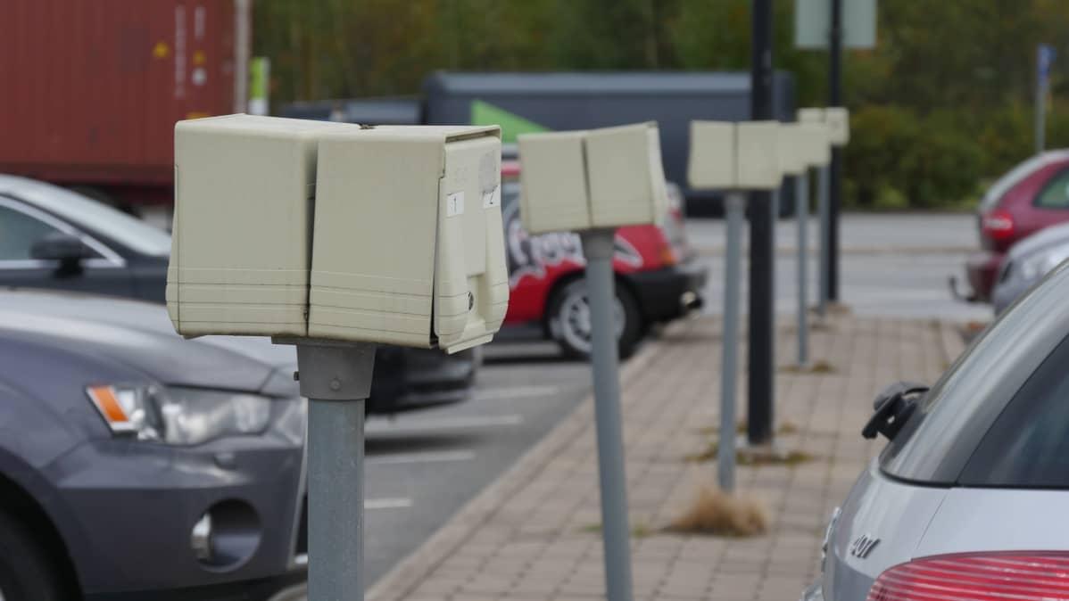 Parkkipaikka, jossa rivissä auton lämmitystolppia.