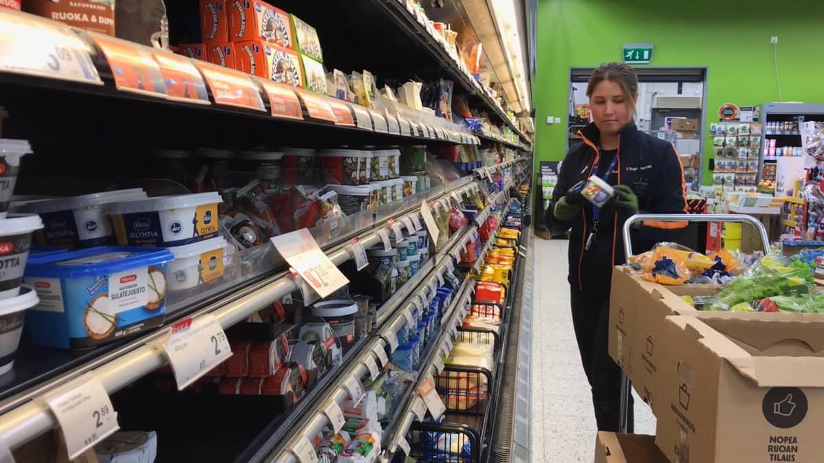 Kaupan työntekijä keräilee ruokatarvikkeita pahvilaatikoihin
