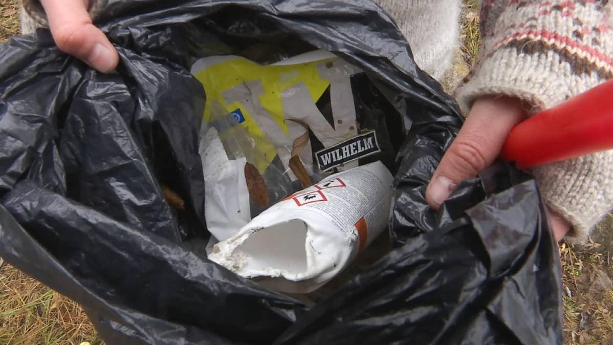 Luontoyrittäjä Tytti Bräysy kerää retkillään roskia luonnosta, kuvassa makkarapaketteja muovipussissa
