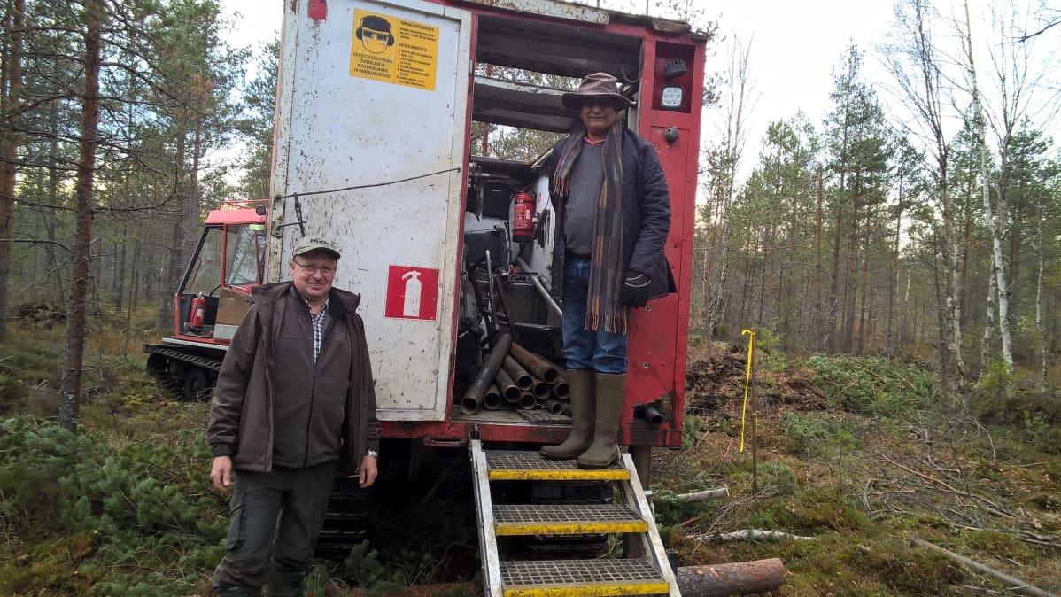 Kaksi miestä poseeraa pakettiauton takana