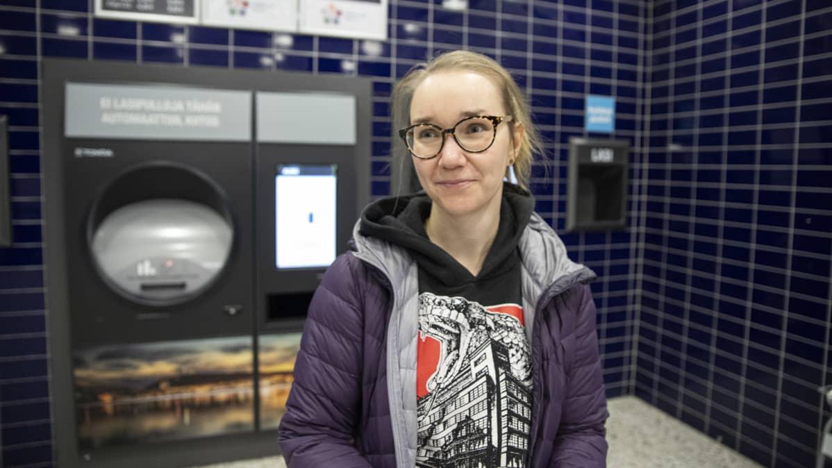 Nainen pullonpalautusautomaatin luona.