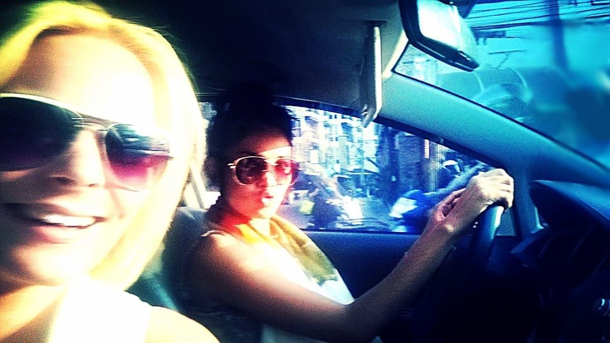Aurinkolasipäiset naiset istuvat auton etupenkeillä.
