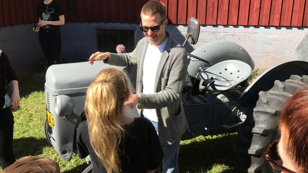 Olavi Uusivirta traktorin vieressä jakamassa nimmareita koululaisille