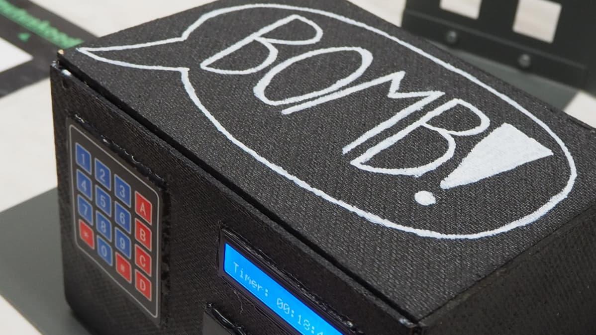 """Pelissä käytetty supertietokone, joka vaatii purkukoodin. Tietokone näyttää mustalta laatikolta, jonka edessä on numeronäppäimet ja päällä lukee """"bomb""""."""