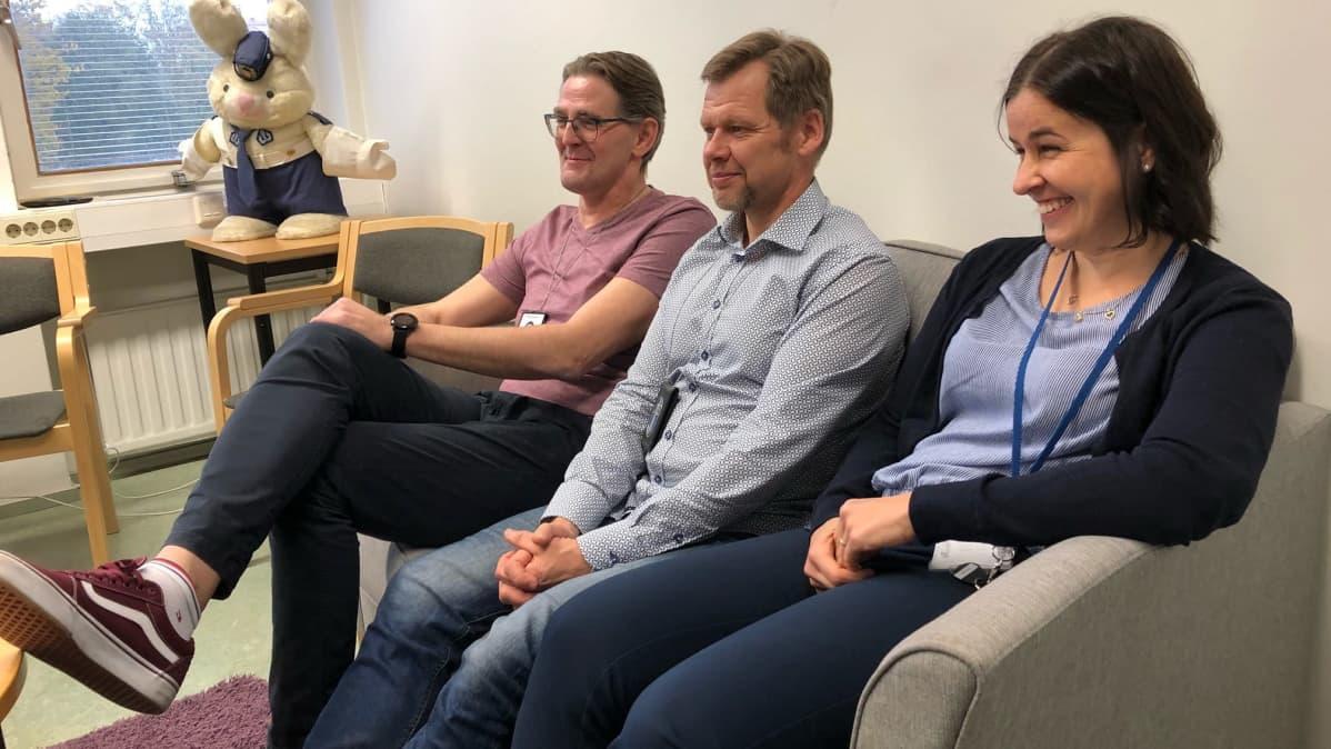 Yksi nainen ja kaksi miestä istuu hymyllen sohvalla.