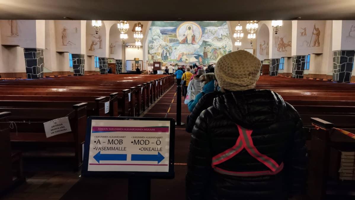 Kirkkoherranvaalien äänestäjät jonottavat Rovaniemen kirkon keskikäytävällä.