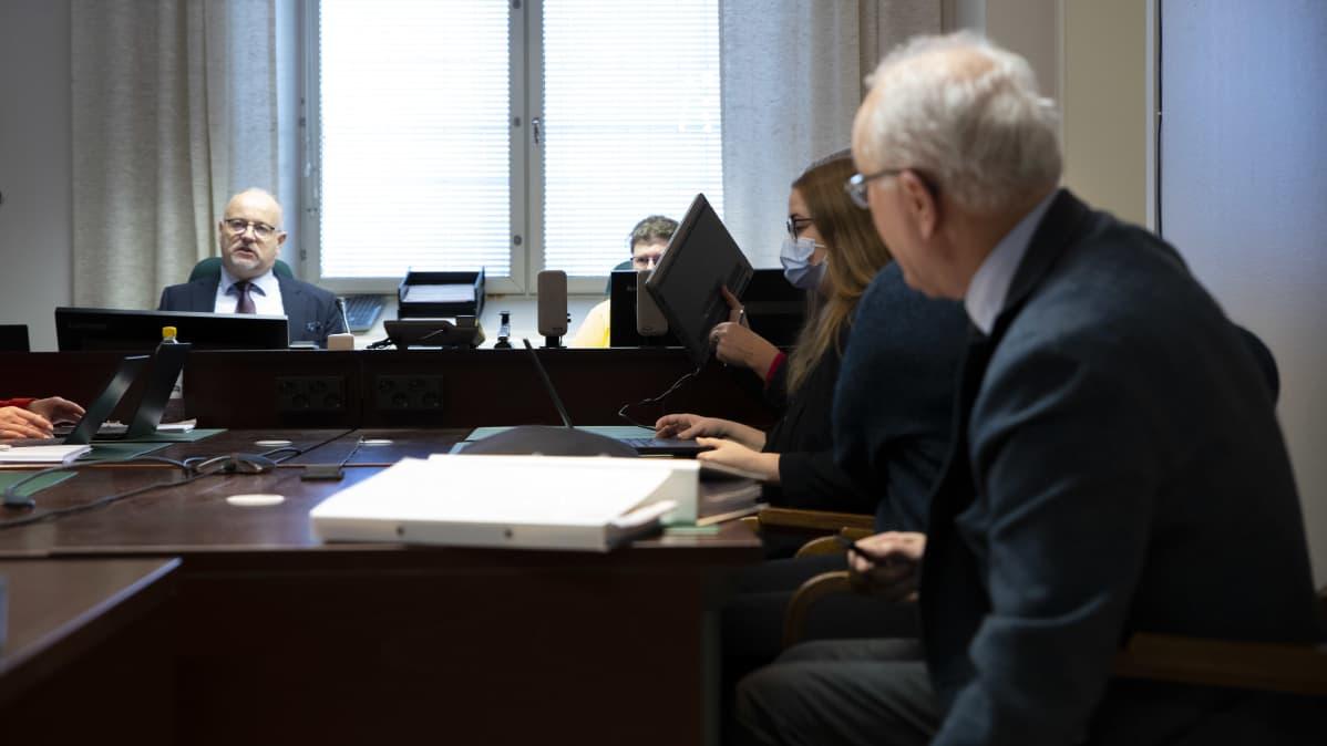 Ihmisiä istuu oikeudenkäynnissä
