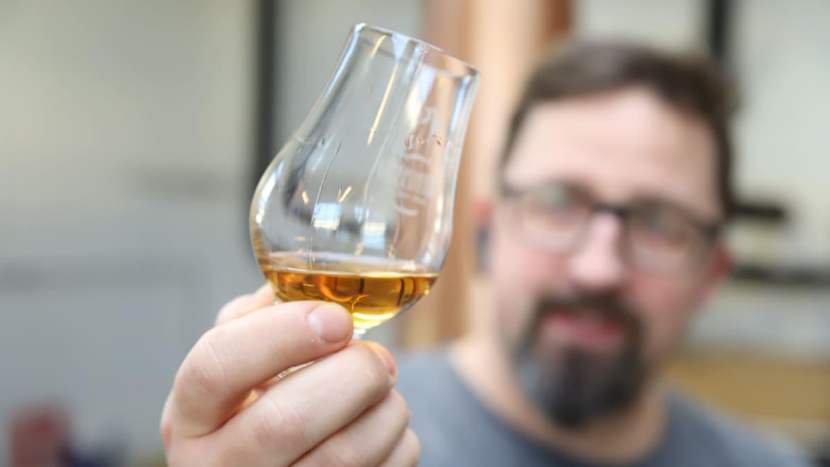 Viskimestari tarkastelee näyteannosta viskilasissa