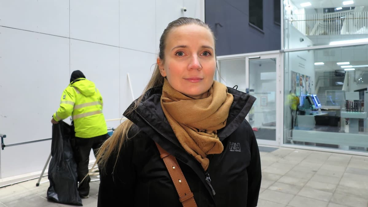 Nainen katselee kameraan koulun sisäänkäynnin edessä