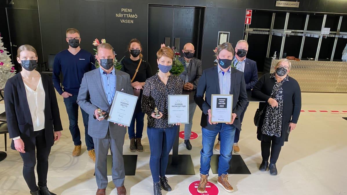 Ihmisiä kunnikirjat käsissä ja maskit naamalla.