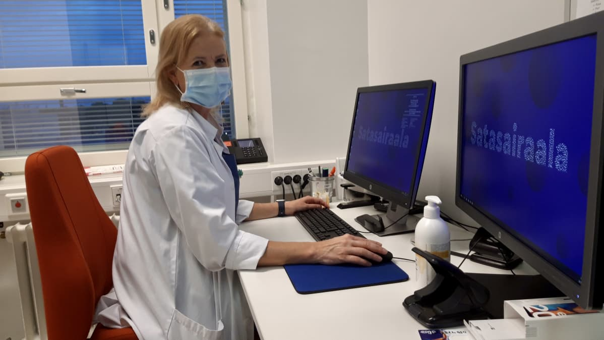 Lääkäri tietokoneen ääressä.