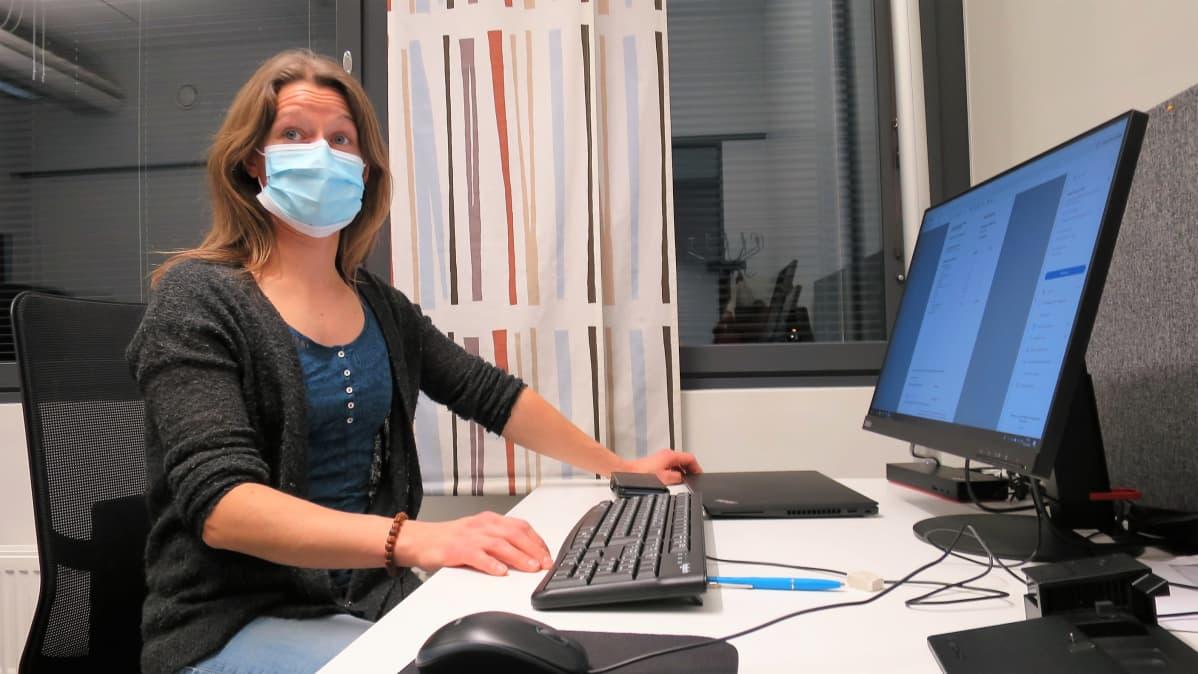 Tummahiuksinen nainen työskentelee