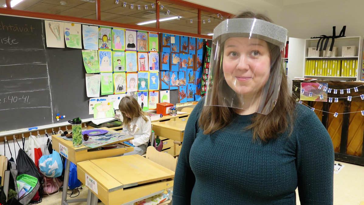 Luokanopettaja maski kasvoillaan seuraa käsityötunnilla käpyranssien tekoa
