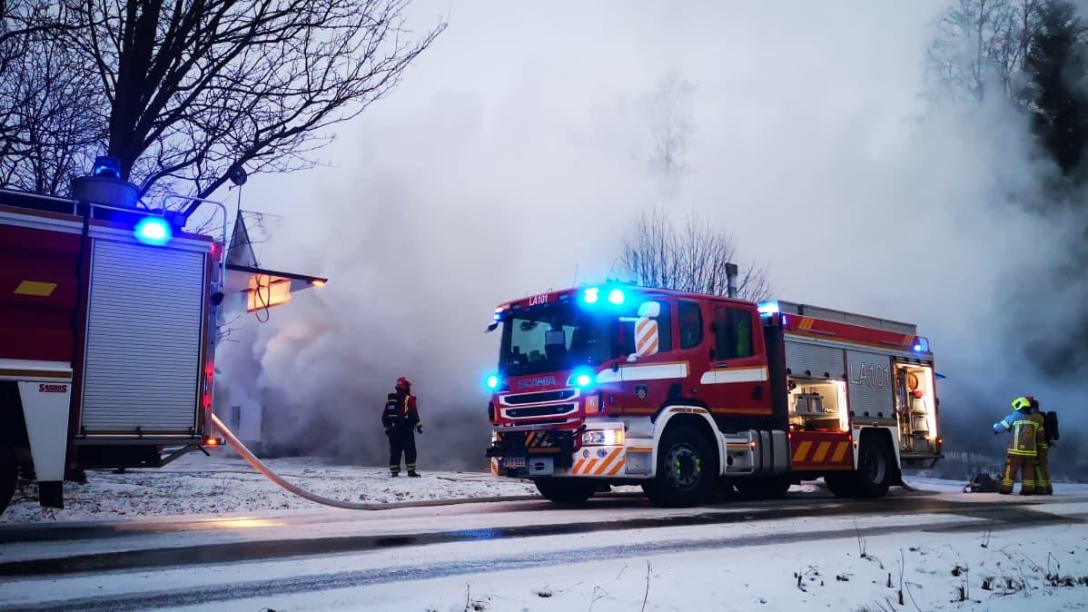 Kaksi paloautoa ja pelastushenkilökuntaa savuisessa ja talvisessa maisemassa.