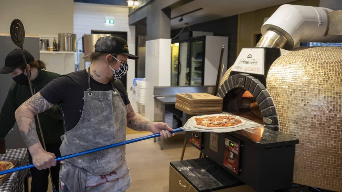 Mies laittamassa pizzaa uuniin.
