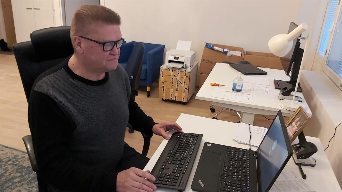 Timo Tersa istuu toimistossaan tietokoneen äärellä.