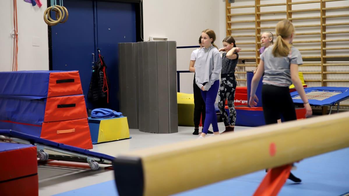 tytöt jonottavat trampoliinille telinevoimistelutreeneissä