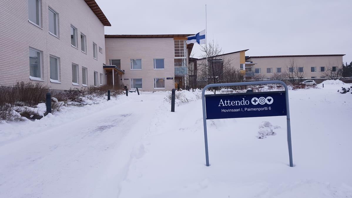 Suomen lippu heiluu puolessa tangossa hoivakodin pihalla