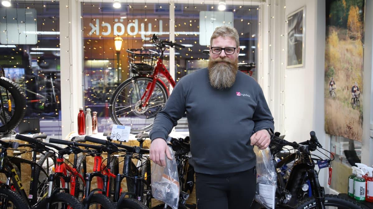 Marvin Kiviniemi nojailee polkupyörärivistöön. Taustalla on näyteikkuna, jossa punainen pyörä ja jouluvalot