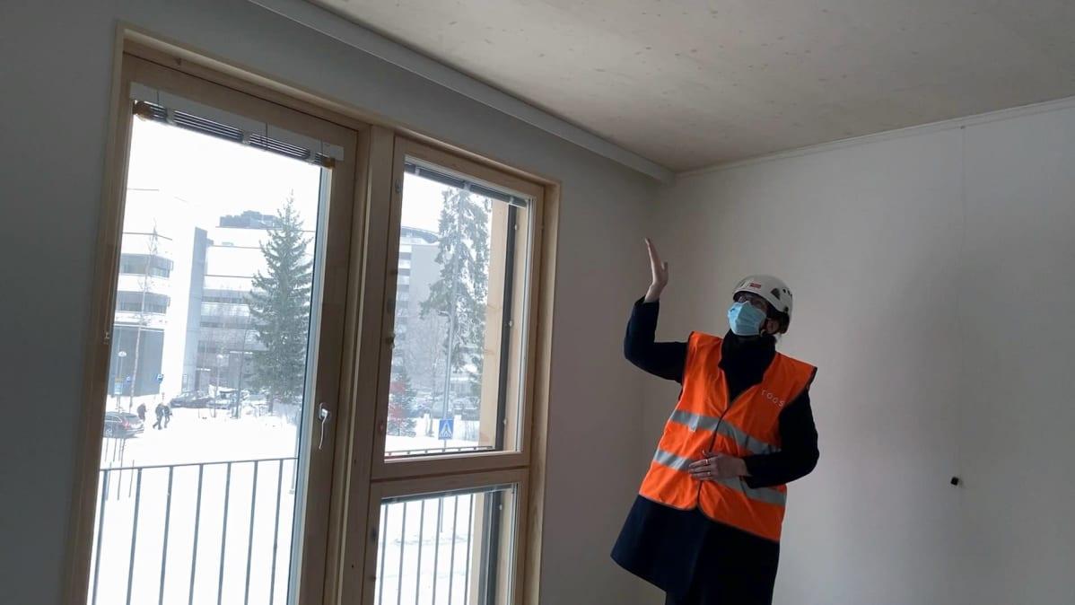 TOASin toimitusjohtaja Kirsi Koski osoittaa opiskelija-asunnon puista kattoa