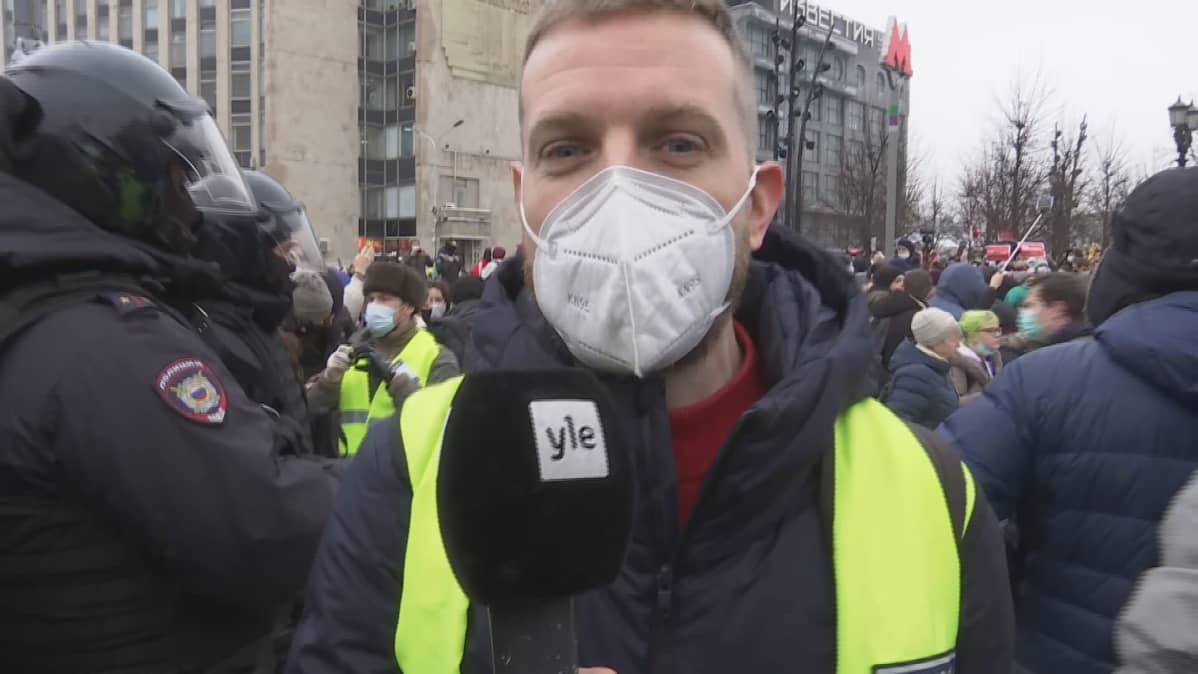 Kirjeenvaihtaja Erkka Mikkonen huomioliiveissä, taustalla mellakka-asuisia poliiseja ja mielenosoittajia