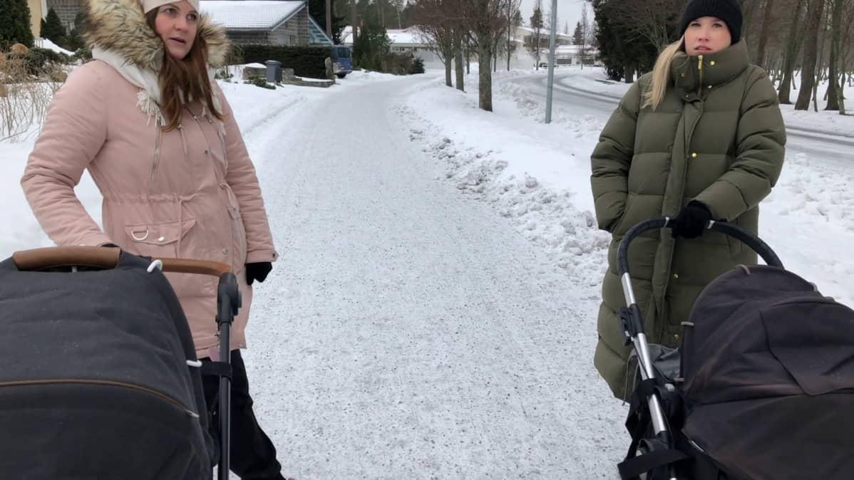 Naiset juttelevat lastenrattaiden kanssa lumisella jalkakäytävällä