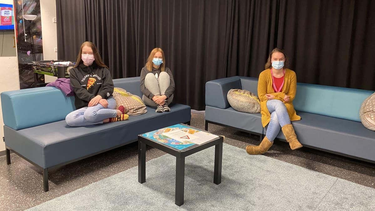 Aikuinen ja kaksi nuorta naista istuvat nuorisotilan sohvilla