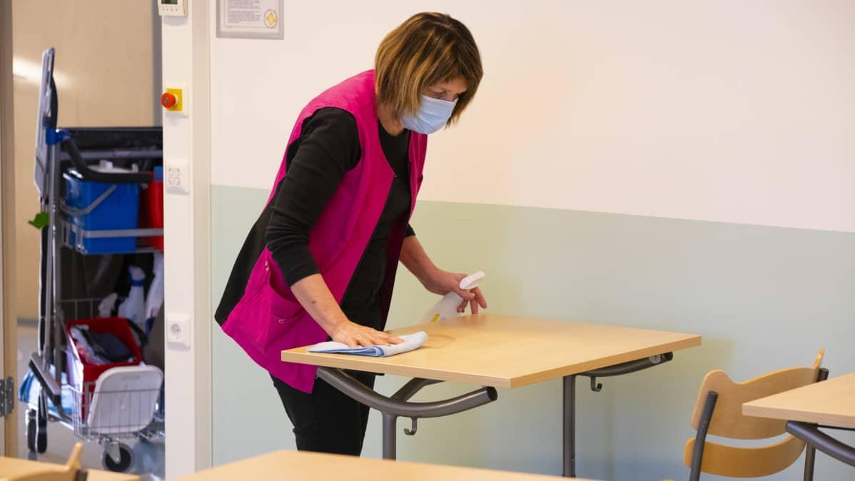Tervolan lukion siivooja Raisa Ranta luutuaa luokkahuoneen pulpettia