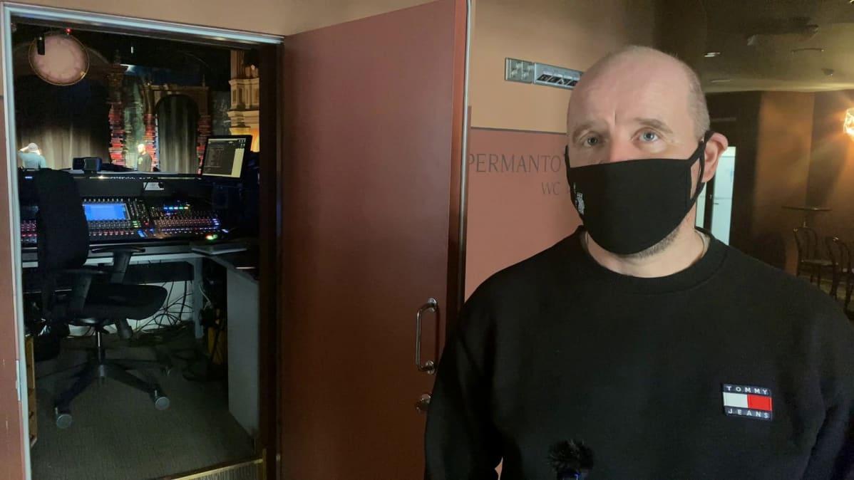 Mies katsoo kameraan päin maski kasvoilla