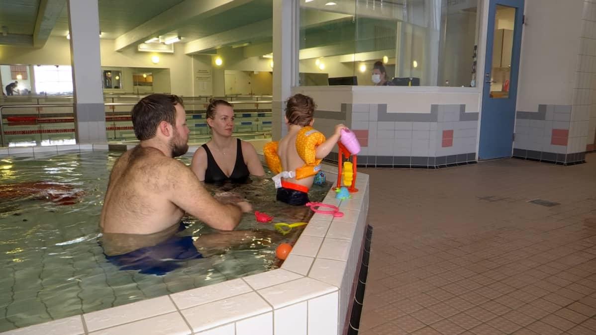 Perhe, 2 aikuista ja 1 lapsi lasten altaassa Padasjoen uimahallissa