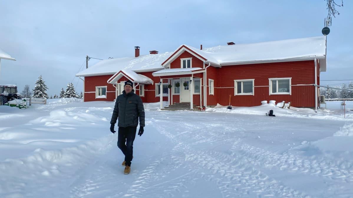 Kuusamolainen Tane Siikaoja hirsitalonsa edustalla.