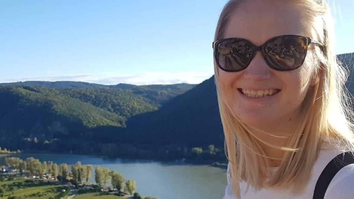 Mari Pollarin kasvokuva. Päässään hänellä on aurinkolasit, ja hän hymyilee. Taustalla näkyy jokimaisema.