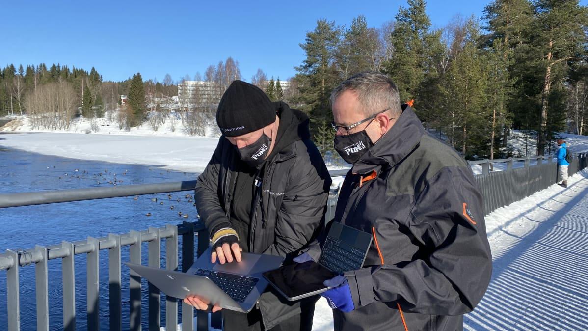 Projektipäällikkö Marko Karvonen ja kuvaaja Ilkka Mukkala tutkimassa kuvapankin kuvia Kajaanissa.