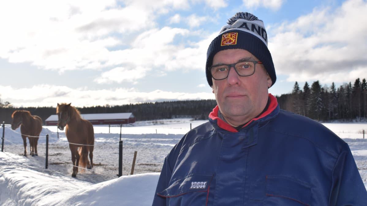 Kankaanpään seudun tykistökillan puheenjohtaja Kimmo Tuomi seisoo ulkona talvella kaksi hevosta seisoo taustalla syömössä