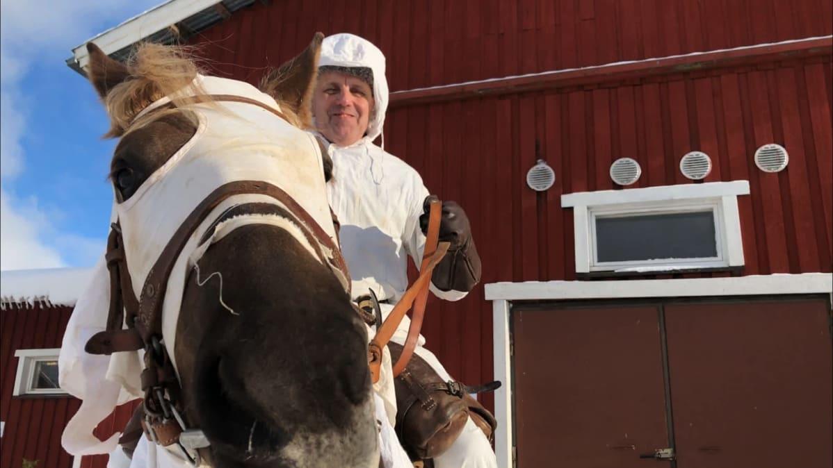 Ratsuri Matti Peurala istuu hevosen selässä