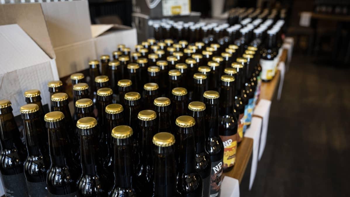 Paljon olutpulloja pöydällä.