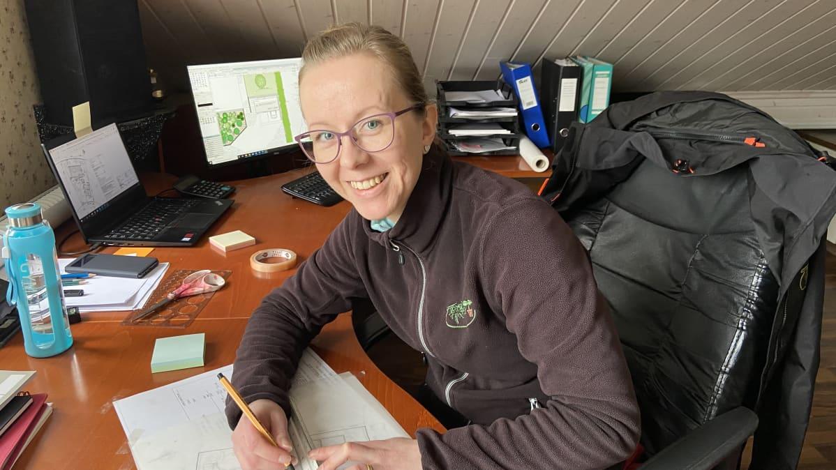 Kuvassa suunnitteluhortonomi Anna-Maija Furu työpöytänsä ääressä piirtämässä pihasuunnitelmaa.