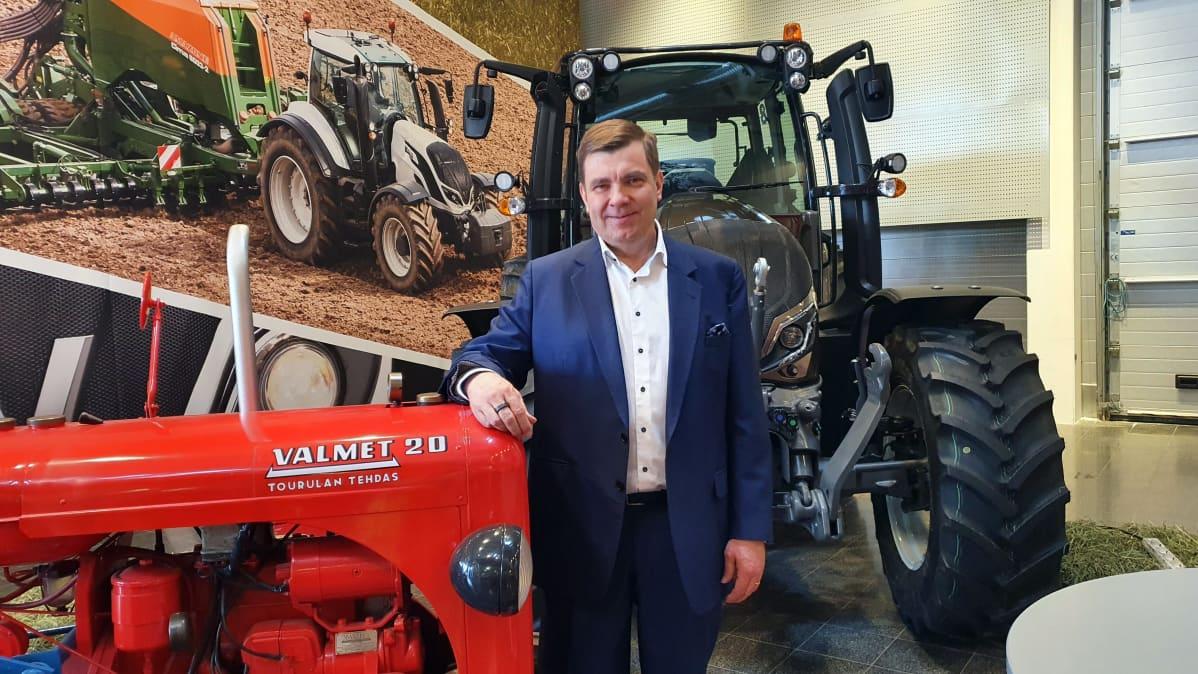 Valtran toimitusjohtaja Jari Rautjärvi poseeraa vanhan ja uuden traktorimallin edessä Valtran Suolahden tehtaalla.