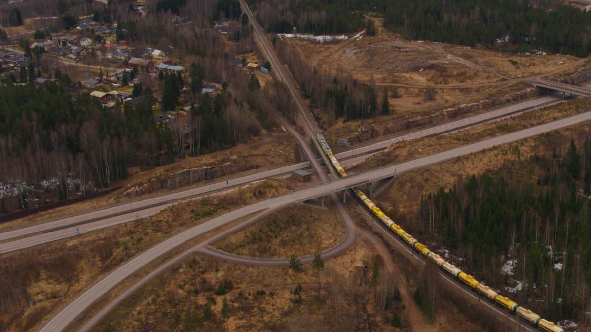 Ilmakuva noin kilometrin pituisesta tavarajunasta, joka kulkee raiteilla autoteiden risteillessä.