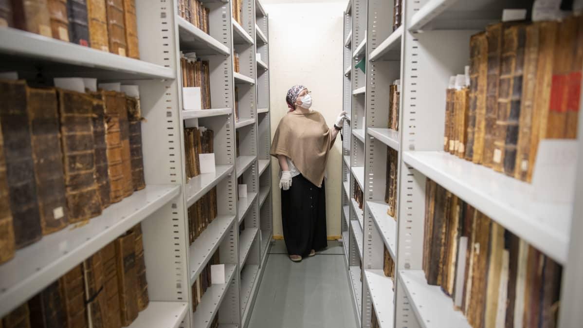Kirjastonhoitaja Virva Suvitie Valamon luostarin kirjaston hyllyjen välissä.